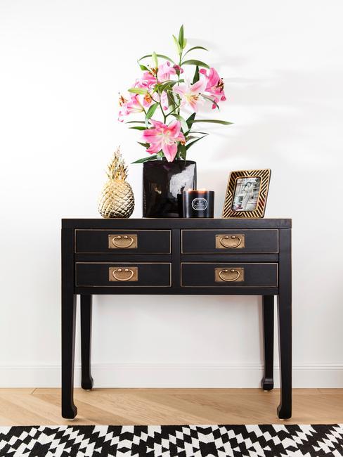 Zwarte sideboard met decoratie van boeket bloemen, fotolijstje en decoratieve ananas