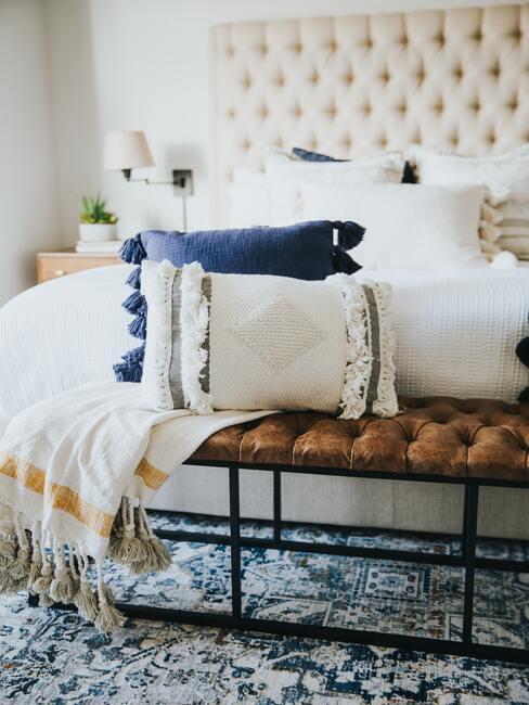 Een slaapkamer met een tapijt in blauwtinten en een bankje met decoratieve witte en blauwe kussens en een deken.