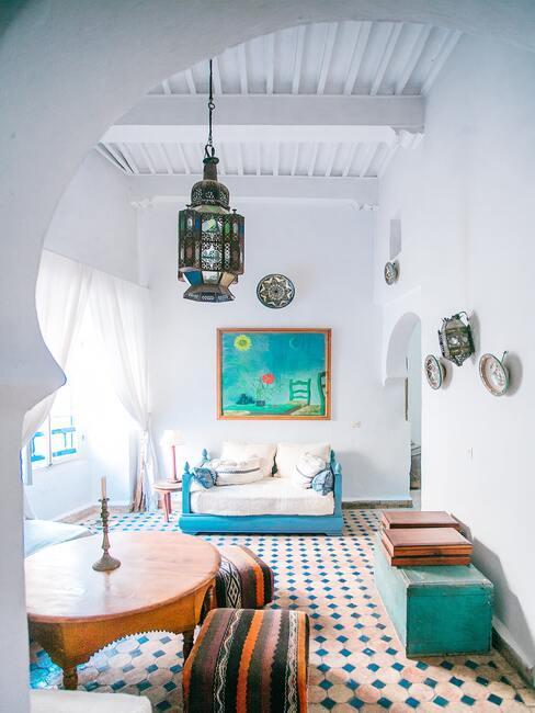 Lichte kamer met patchwork-tegels en een blauwe bank met witte kussens