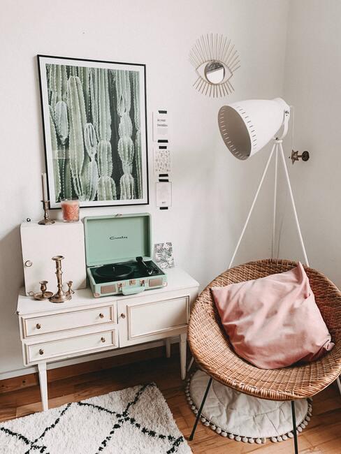 Licht vloerkleed met een geometrisch patroon naast het wit van het dressoir en de rotan stoel met een roze kussen naast een witte staande lamp