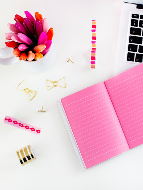 Roze boek, met roze pennen en tape op witte tafel