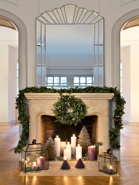 Kerstkrans op de open haard naast de kaarsen