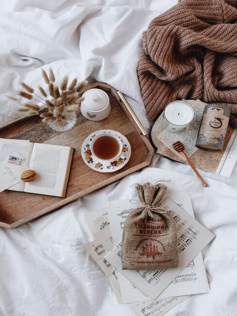 Kerstbrunch organiseren: een kopje thee geserveerd op een houten dienblad met een doorzichtige vaas met bloemen