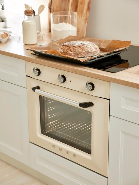 Oven schoonmaken witte oven in witte keuken met licht houten keukenblad