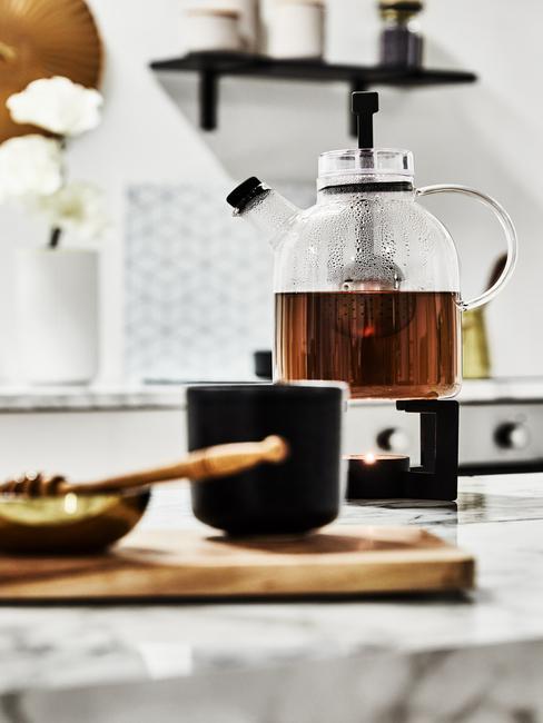 Zwarte pot naast een glazen theepot