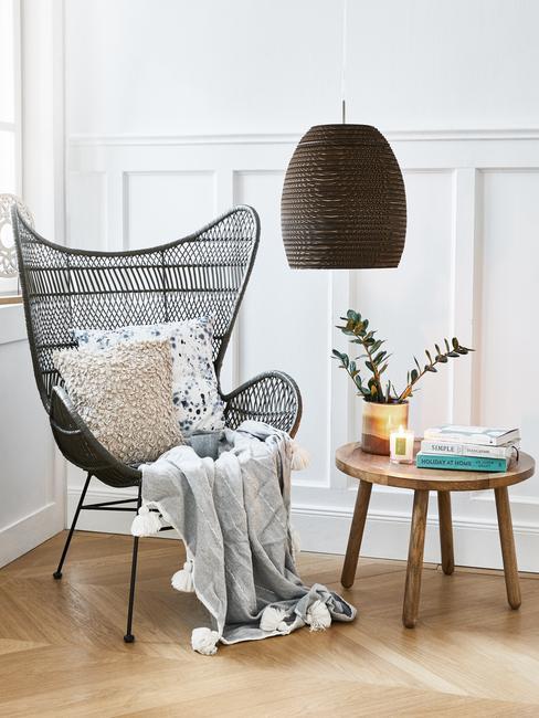 Zwarte rotan fauteuil met sierkussen en zachte plaid naast houten bijzettafel met accessoires en ornamenten