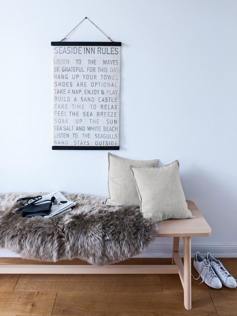 Houten bank met schapenvacht en zachte kussens en print aan de witte muur