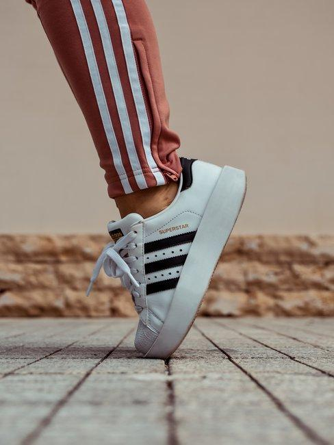 Adidas superstar sneakers op tenen met rode adidas trainingsbroek