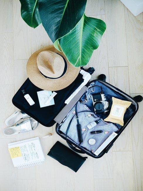 Open koffer van boven op licht houten vloer met inhoud en rieten hoed