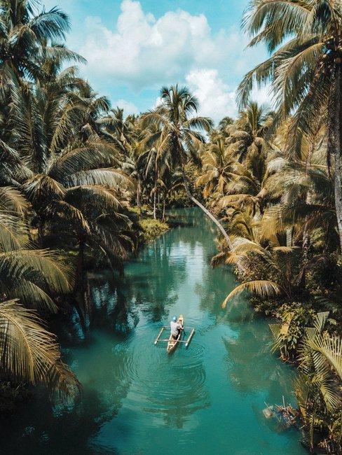 Blauwe rivier door groene jungle man in houten kano