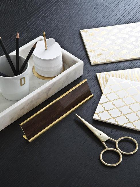Donker houten tafel met gouden assecoires en marmeren bakje met schaar en pennen