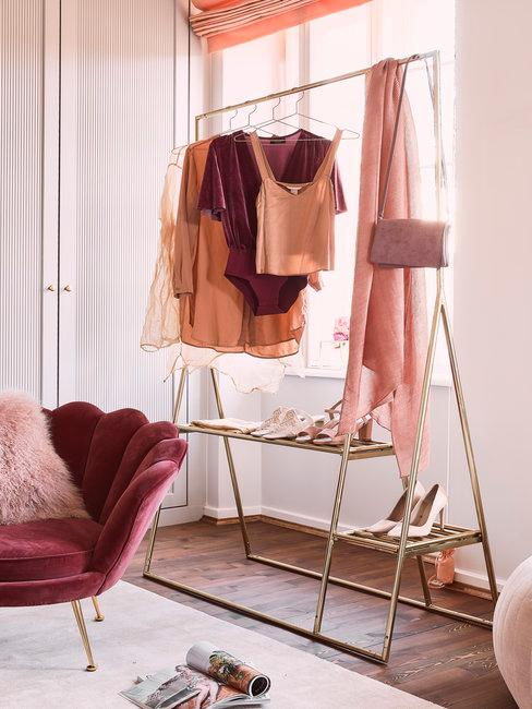 Gouden kledingrek met roze en nude tinten op houten vloer met vloerkleed en roze stoel