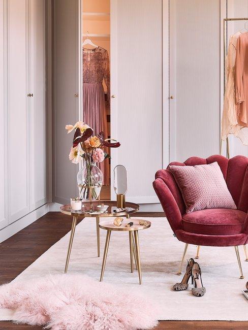 Walking closet met paarse stoel en zachte tinten kleding en gouden tafel