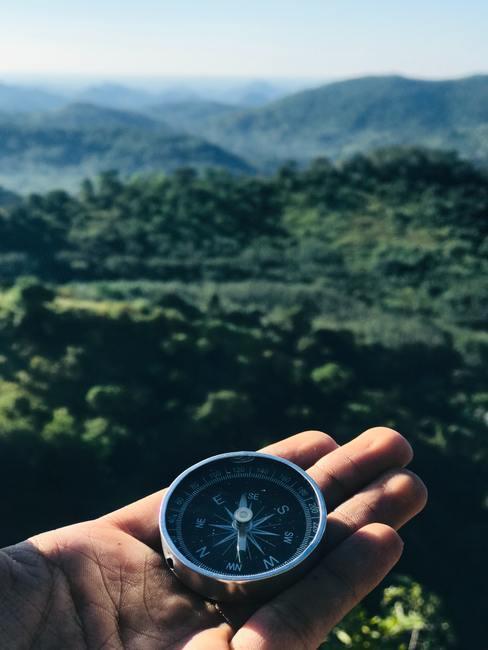 Compas in hand met uitzicht op groene bergen