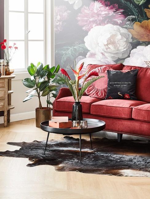Frans interieur met een bank en sierkussens en een salontafel met bloemenvazen en een zwart vloerkleed.