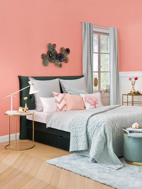 Frans interieur in perzikkleuren met een zwart bed en grijs pastel linnen en goudkleurig nachtkastje.