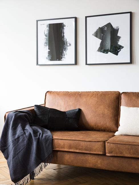 Witte muur met twee zwart wit schilderijen met cognac kleur bank