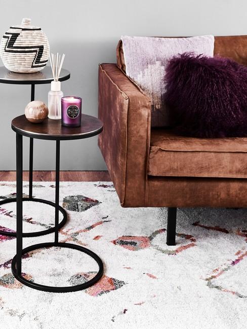 Wit vloerkleed met patroon hoek van een cognac kleur bank en ronde bijzettafels