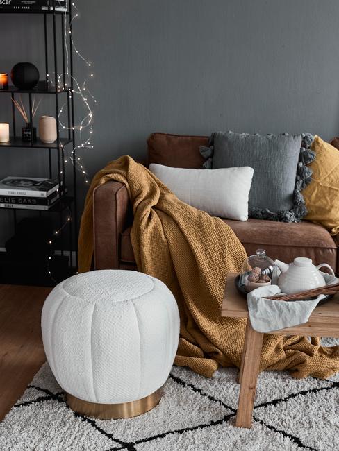 Grijze kleur muur ben cognac kleurige bank en laken met witte poef