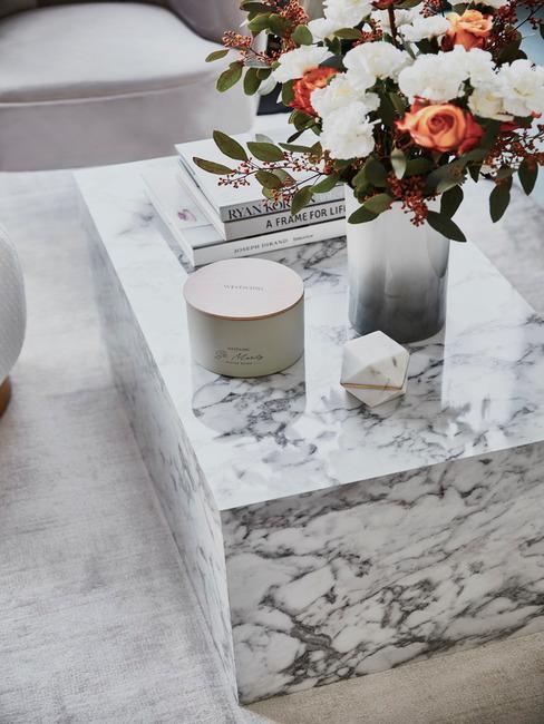 Marmeren salontafel met bos bloemen op wit vloerkleed