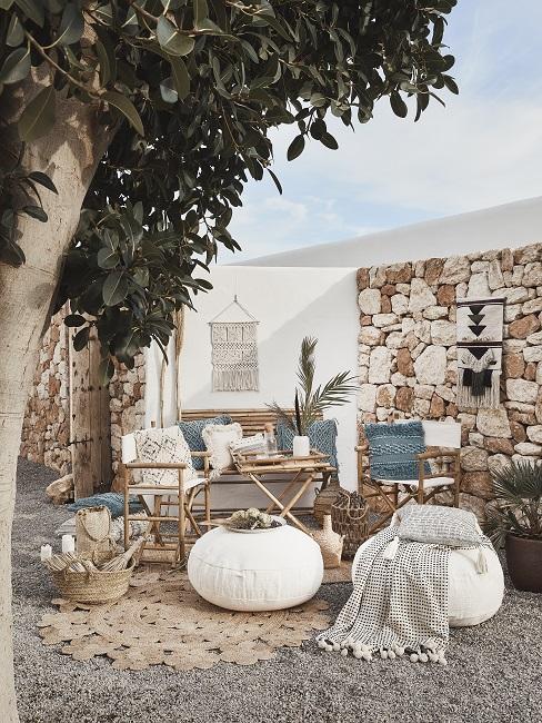 Inbiza stijl tuin inspiratie met grote boom en tegelmuur met bamboe meubels