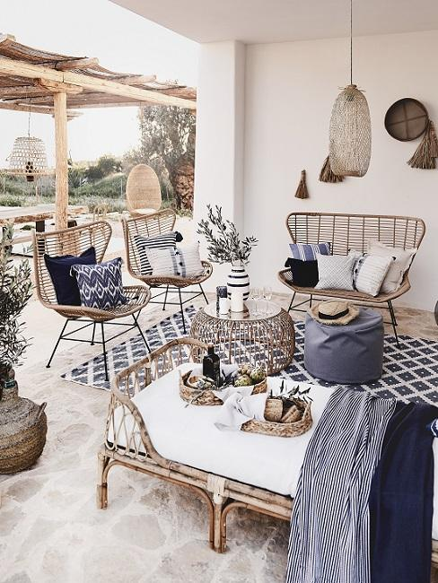 Mediterrane tuin met minimalistische rotan meubels met blauwe accessoires