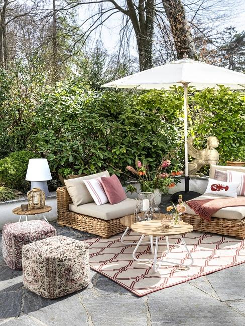 Kleine tuin inrichting met loungebank en parasal en houten accessoires
