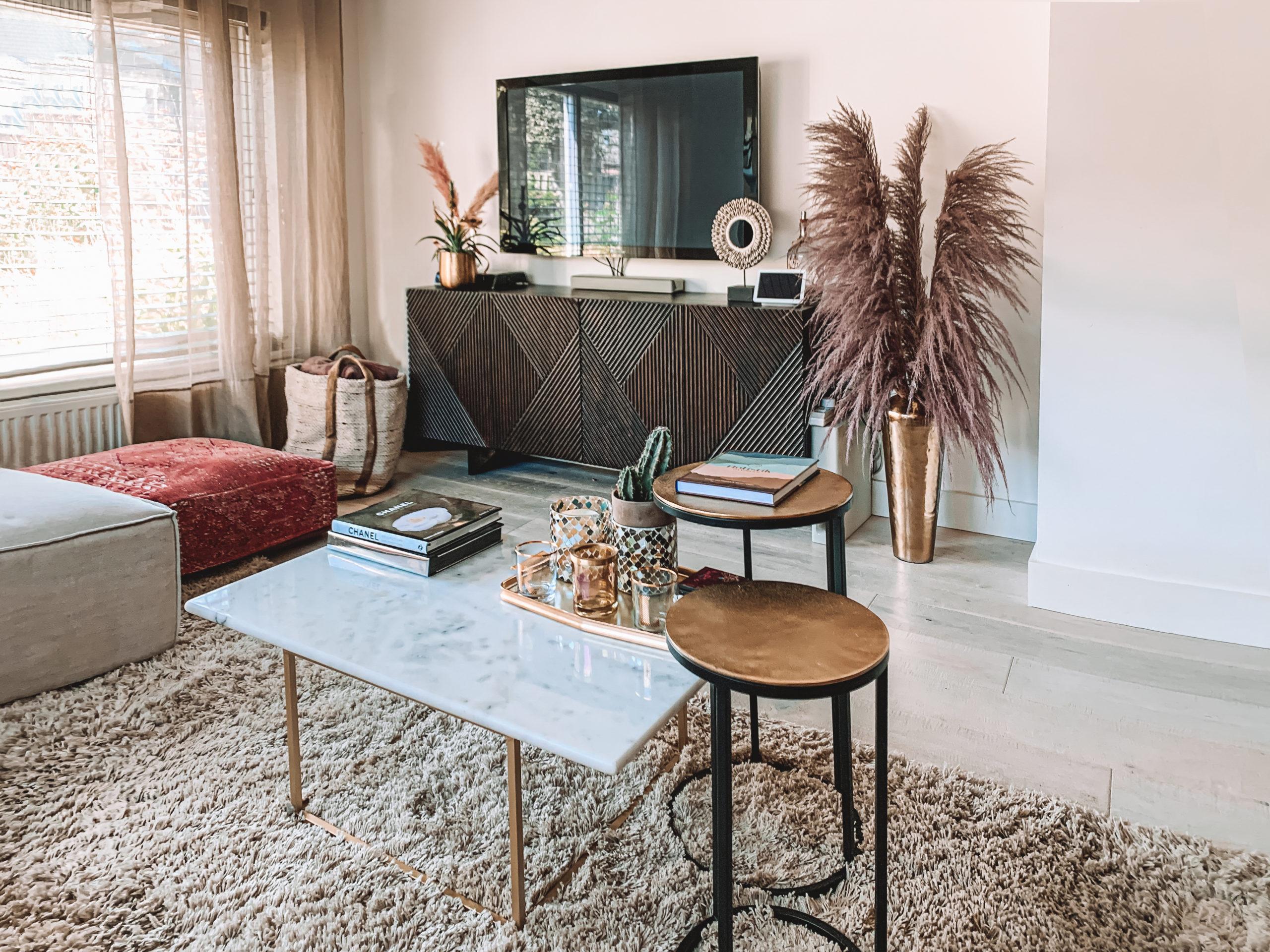 Woonkamer met hoogpolig vloerkleed en televisie op houten dressoirkast
