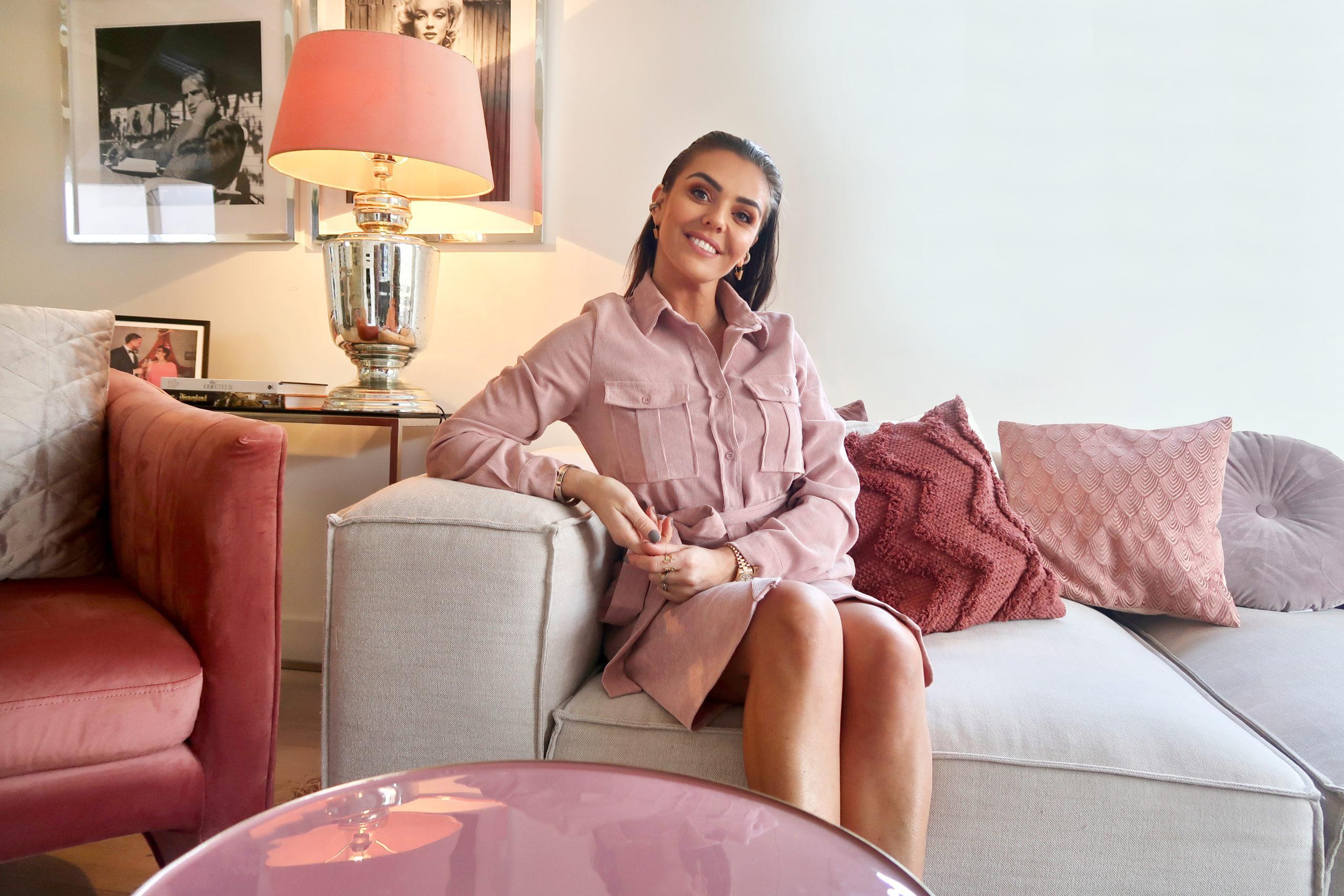 Laura Ponticorvo zitten op haar grijze Lennon bank met oude roze accessoires