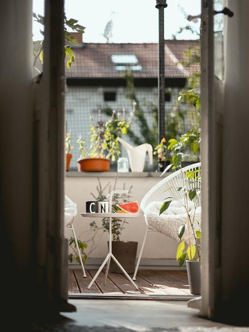 Aanzicht vanuit huis naar het balkon met witte stoelen en witte muur