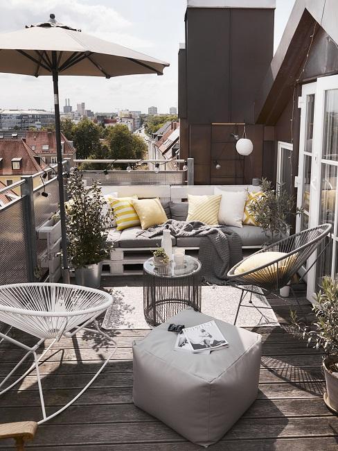 Lage balkonbar voor loungebank van pallets en gevlochten witte en zwarte stoelen