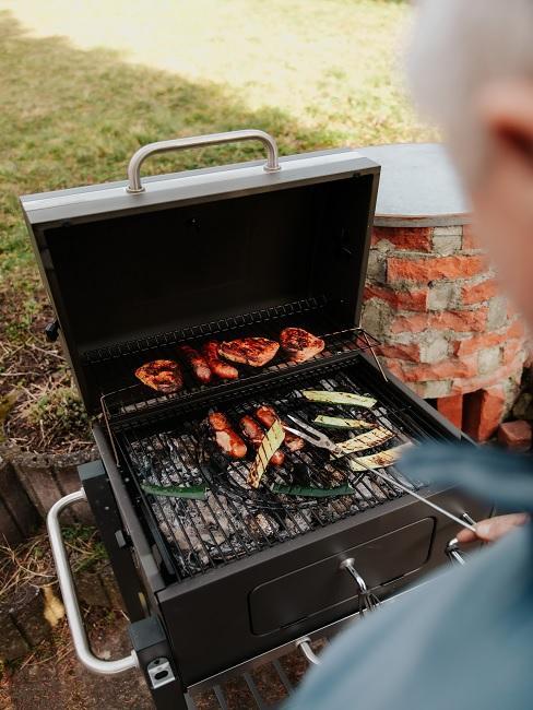 Barbecue in de tuin met worst op de grill