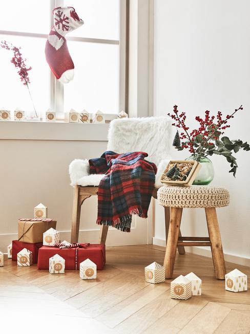 Fauteuil bekleed met witte schapenvacht en houten kruk met bloemen in vaas en waxinelichten op de vloer