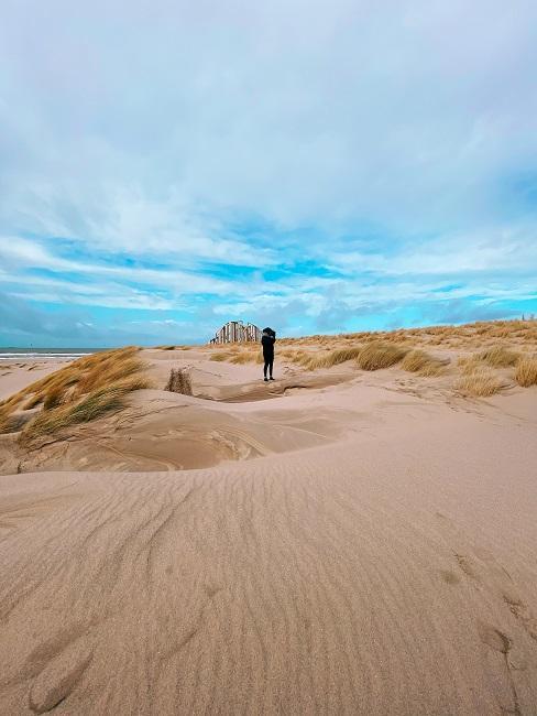 Strandvakantie duinen met wandelende persoon