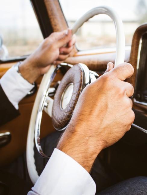 Stuur oldtimer auto met twee mannelijke handen in pak