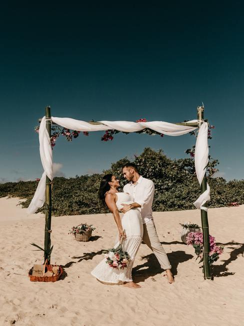 Bruidspaar op het strand onder een decoratief frame in boho stijl