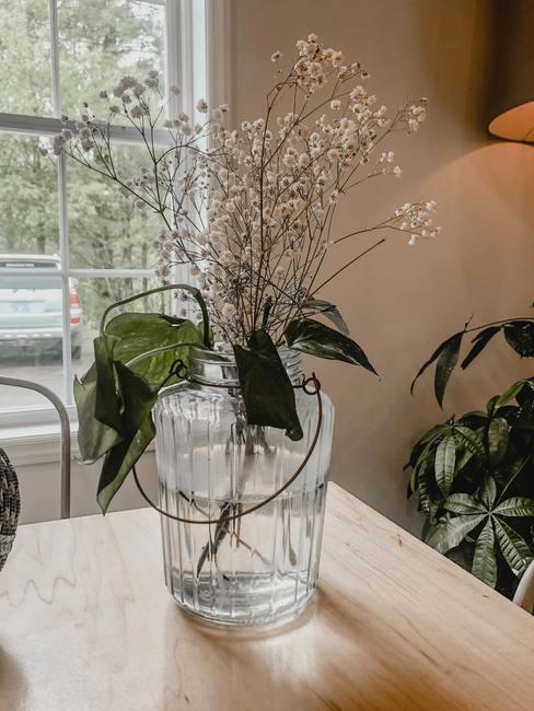 Woonkamer in minimalistische stijl met een transparante glazen vaas en takdecoratie