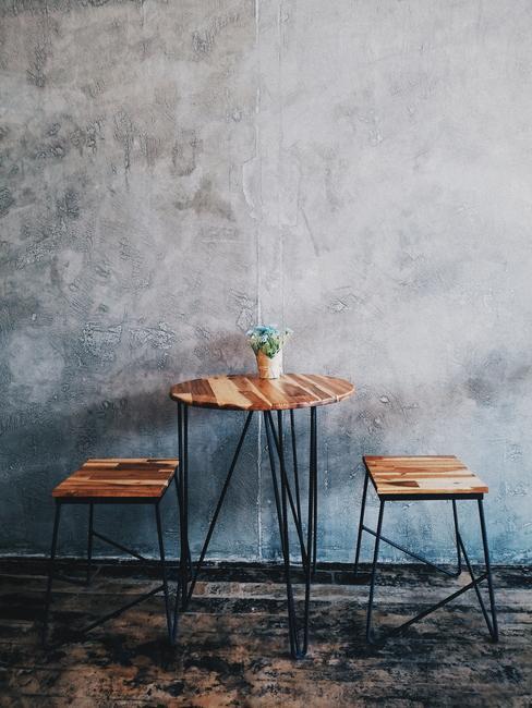 Houten tafel en twee krukken op de achtergrond van grijze muur