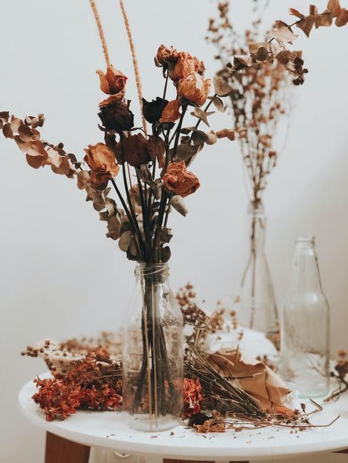 Decoratie van gedroogde bloemen in transparante glazen vazen