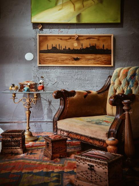Oude houten fauteuil naast de tafel met decoratie en ingelijste print op de muur