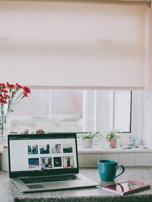Laptop en mok op de tafel tegen de achtergrond van bloemen in een vaas