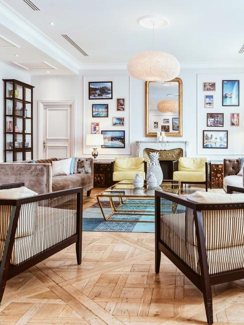 Modern woonkamer in wit met een decoratieve vergulde spiegel, veel ingelijste prints en rotan fauteuils