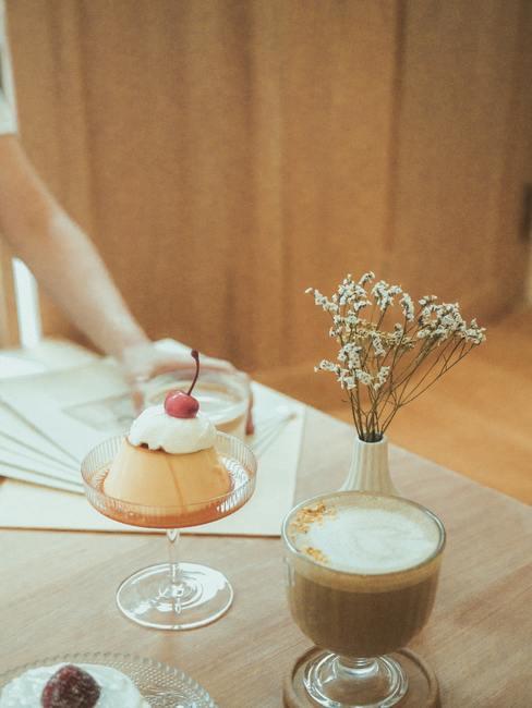 Koffiemok met een taartje en witte vaas op houten stoel in vintage stijl