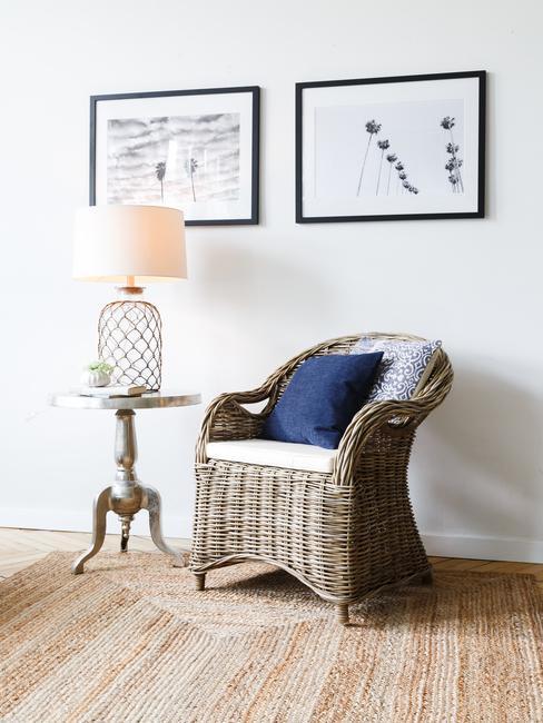 Rotan fauteuil met witte zitkussen en blauwe sierkussens naast bijzettafel met tafellamp en twee printen op witte muur
