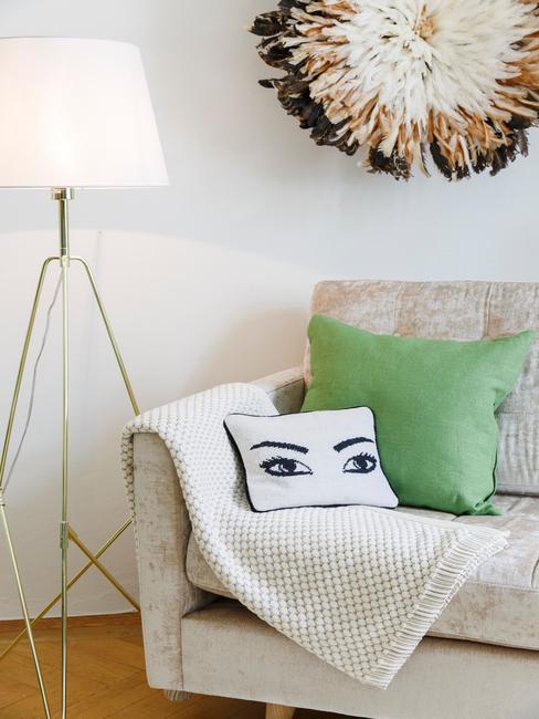 Close-up beige zitbank met groene en witte sierkussens met vloerlamp en decoratief object op muur