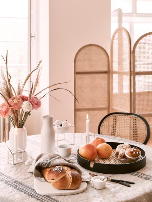 Mid century modern keukentafel met gedekte tafel en rotan stoelen en scherm