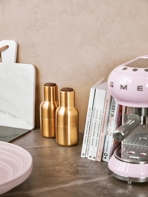 Keukenblad met gouden peper en zout stel naast roze koffiemachine