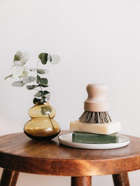 zeep en borstel met vaas en bloem op houten bijzettafel