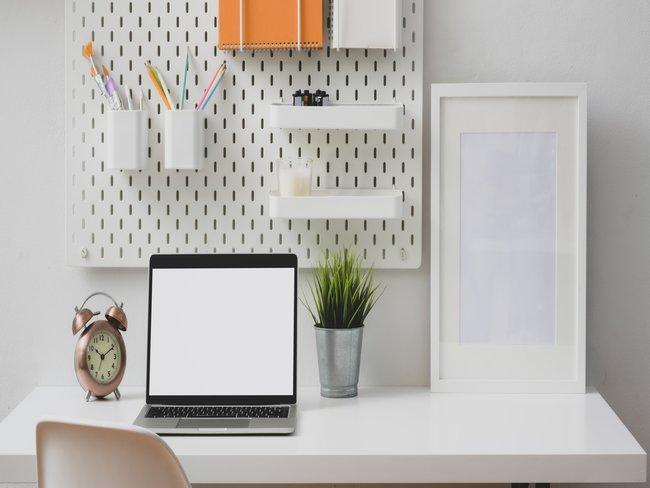 Home office met laptop en wandrek met bureaubenodigdheden voorjaarsschoonmaak