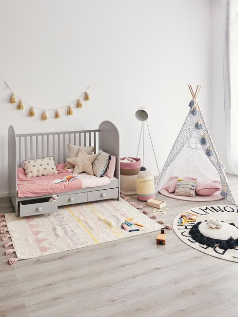 Muurdecoratie babykamer:een grijs bedje naast het tapijt en de tipi-tent